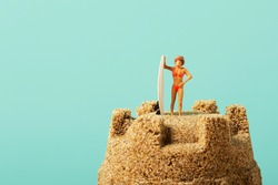 closeup of a miniature woman in swimsuit, standing next to a surfboard, on the top of a sandcastle, against a blue background with some blank space on the left