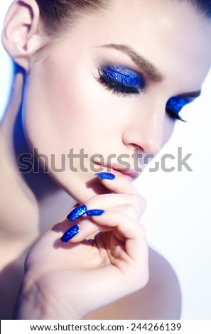 Closeup of a model with blue glitter makeup and manicure. Lighting and model look slightly like 90s style.