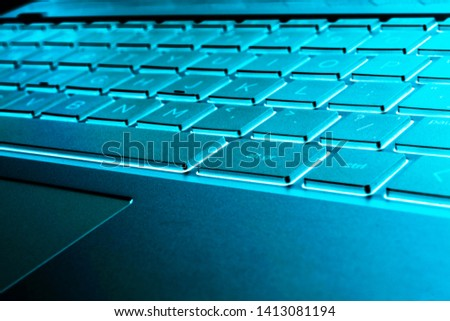 Closeup of a modern silver laptop computer keyboard. Laptop keyboard. Detail of the new and ergonomic computer keyboard. Blue tones stock photo