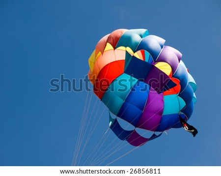 Closeup of a multicolor parasailing balloon with a pirate flag and a beautiful blue sky in background.