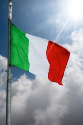 Closeup of a national Italian flag with flagpole, blowing in the wind on a blue sky with clouds and Sunbeams.