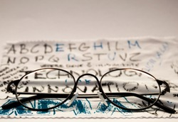 Closeup of a pair of glasses laying on a glasses cleaning cloth. Nopeople