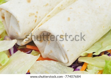 closeup of a pair of mexican burritos with salad