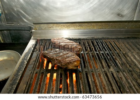 Closeup of a pair of New York Strip steaks cooking over an open flame.