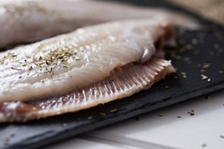 closeup of a pair of raw filleted common sole on a slate tray placed on a rustic wooden table