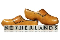 Closeup of a pair of wooden Dutch clogs and the text Netherlands, made of wooden blocks, isolated on white background with reflections.