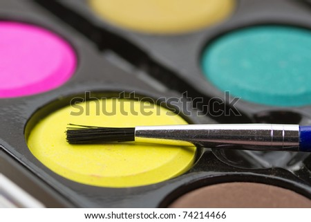 Closeup of a palette of watercolor paints with brush.
