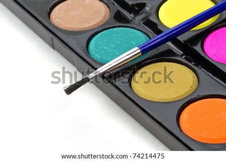 Closeup of a palette of watercolor paints with brush. - stock photo