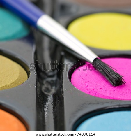 Closeup of a palette of watercolor paints with brush