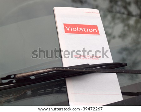Closeup of a parking ticket clamped between the windshield and the wiper blade
