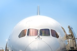 closeup of a passenger jet nosecone and cockpit with doors open