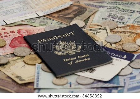 Closeup of a Passport with ticket stubs on top of mixed foreign money including US, Taiwan, Indian, Hong Kong, Honduran, Malaysian and Korean currency