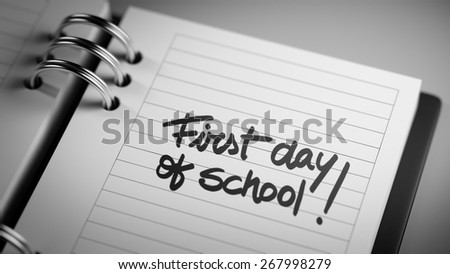 Closeup of a personal agenda marking a day of the month representing a organizing time and schedule. First day of school text note reminder concept. Words First day of school written in Black Marker.