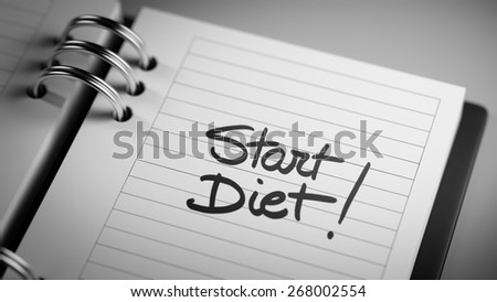 Closeup of a personal agenda marking a day of the month representing a organizing time and schedule. Start Diet text note reminder concept. Words Start Diet written in Black Marker.