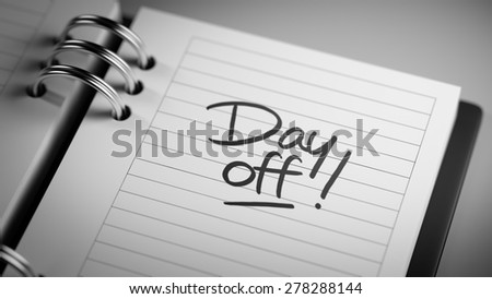 Closeup of a personal agenda setting an important date representing a time schedule. The words Day off written on a white notebook to remind you an important appointment.