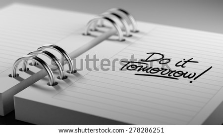 Closeup of a personal agenda setting an important date representing a time schedule. The words Do it Tomorrow written on a white notebook to remind you an important appointment.