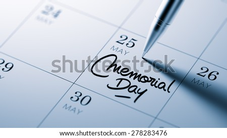 Closeup of a personal agenda setting an important date written with pen. The words Memorial Day written on a white notebook to remind you an important appointment.