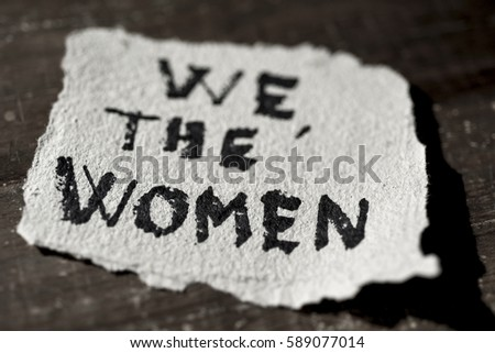 closeup of a piece of paper with the text we the women written in it, on a rustic wooden surface