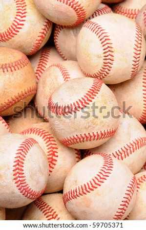 Closeup of a pile of old used baseballs in vertical format.