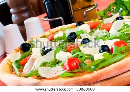 Closeup of a pizza with prosciutto