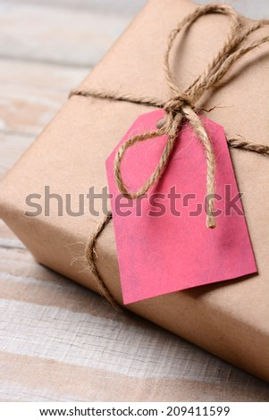 Closeup of a plain wrapped Christmas Present with a red gift tag. The tag is blank. Shallow Depth of field.