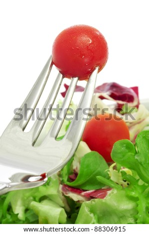 closeup of a plate of salad and a cherry tomato in a fork