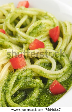 Closeup of a plate with spaghetti, green basil sauce and chopped red pepper