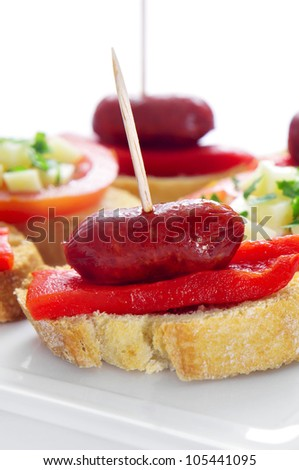 closeup of a plate with spanish pinchos made with chorizos an red pepper