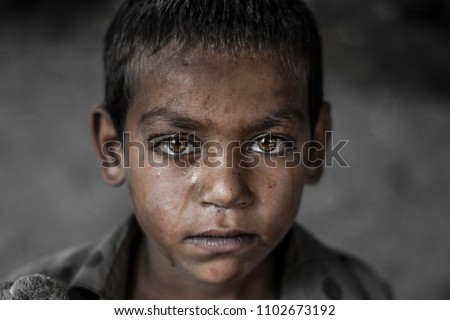closeup of a poor staring hungry orphan boy in a refugee camp with a sad expression on his face and his face and clothes are dirty and his eyes are full of pain Foto stock ©