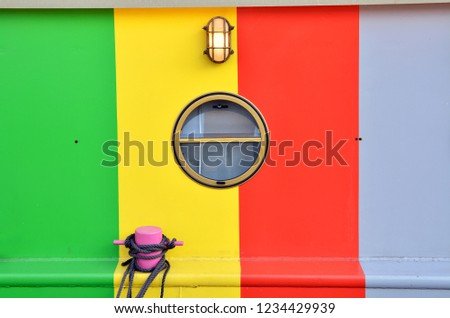 Closeup of a porthole of a barge painted in green, yellow, red and purple stripes.