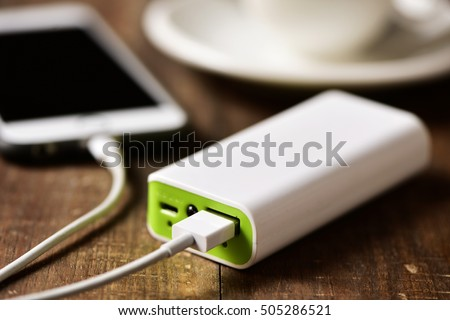closeup of a powerbank charging a smartphone placed on a wooden table next to a cup of coffee #505286521