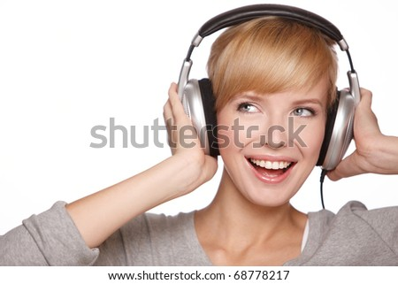 Closeup of a pretty blond female listening to music over headphones