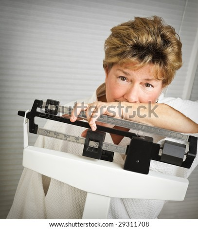 Closeup of a pretty but worried mature woman weighing herself on a medical scale.