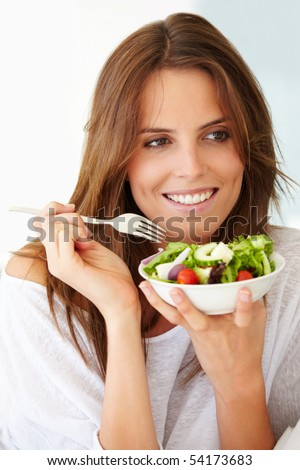 Closeup of a pretty young lady eating fruit salad