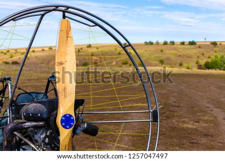 Closeup of a propeller with a motor-paraglider motor against the background of a field. #1257047497