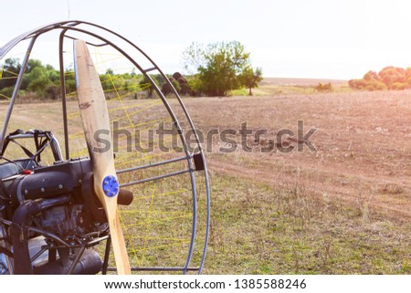 Closeup of a propeller with a motor-paraglider motor against the background of a field. #1385588246
