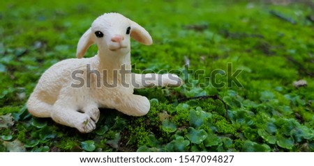 Closeup of a resting lamb figurine on mossy ground #1547094827