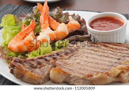 Closeup of a rib steak with shrimp and cocktail sauce
