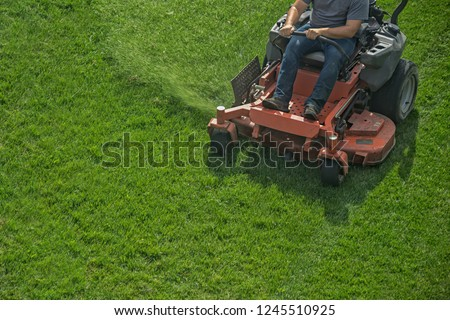 Closeup of a riding landscaper on the lawn mower cutting the grass