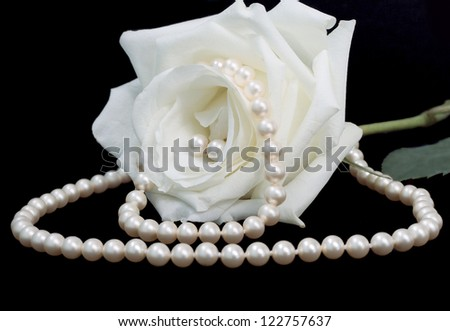 closeup of a rose with pearl set - earrings, bracelet and necklace - on the black background
