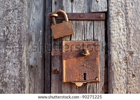 Closeup of a rusty padlock on a wooden door