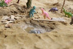Closeup of a scenery made in a sand pit by a child, displaying dinosaur figures between sand, water, wood pieces, narrow depth of field, macro photography