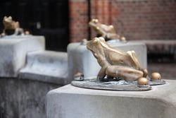 Closeup of a sculpture of a frog made of bronze.