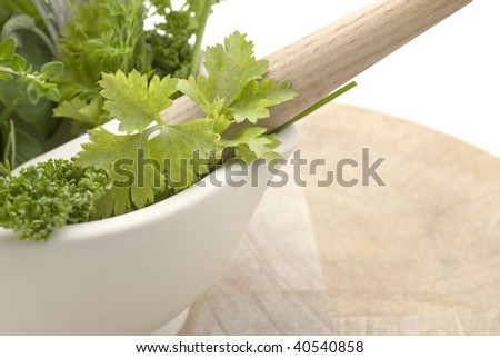 Closeup of a selection of herbs in a cream coloured mortar with pestle on worn wooden chopping board.  Subject cuts off at left edge of frame.  Isolated against white background.