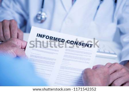 closeup of a senior caucasian man, at the doctors office, reading an informed consent document in front of a caucasian doctor man, in a white coat, sitting both at the doctors desk