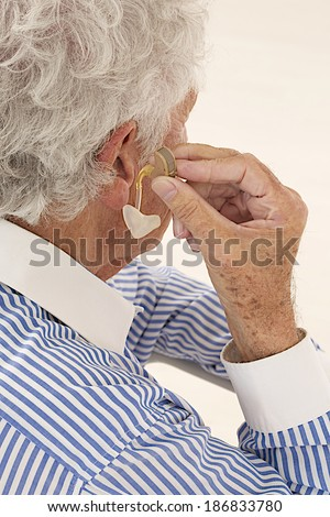 Closeup of a senior  man inserting a hearing aid in her hear. Focus on the hearing aid.