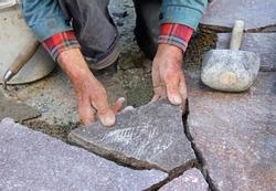 closeup of a senior, paving a patio with natural stones