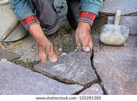 closeup of a senior, paving a patio with natural stones