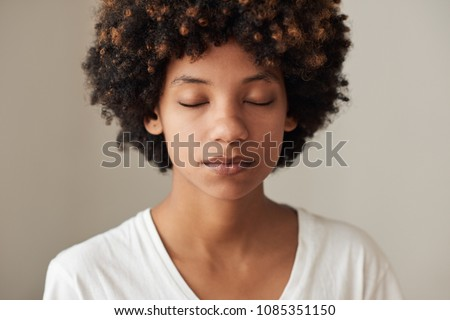 Closeup of a serene young African woman with an afro and natural complexion standing with her eyes closed against a gray background #1085351150
