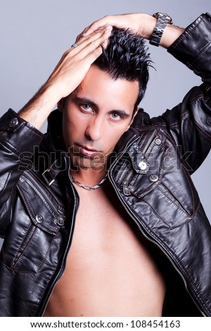 Closeup of a sexy man looking to the camera, wearing a leather jacket and showing his chest. The guy is looking mysterious and sexy while touching hair like oldies. Concept of lifestyle and maleness. - stock photo